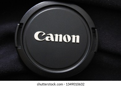Moscow, Russia - March 25, 2019: Canon camera lens cap close up view. Canon corporation brand logo on the cap cover for camera photo and video equipment. Detailed view of modern black Canon camera cap