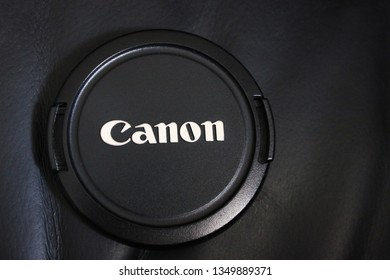 Moscow, Russia - March 26, 2019: Canon photo camera lens cap close up top view. Canon corporation brand logo on cap cover for electronic equipment. Detail of famous Canon digital camera isolated
