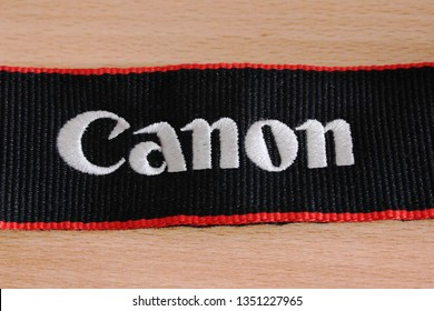 Moscow, Russia - March 27, 2019: Canon photo camera strap close up top view. Canon corporation brand logo on camera belt for electronic equipment. Detail of famous Canon digital camera isolated