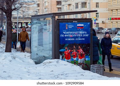 MOSCOW, RUSSIA - MARCH 28, 2018: Public transport stop with advertising billboard of the FIFA 2018 World Cup mundial. Snow on the street. People walk along the sidewalk.