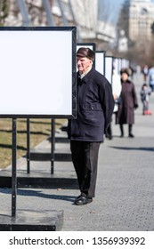 Moscow, Russia - March, 28, 2019: Oldster stands near the advertising stand in Moscow, Russia