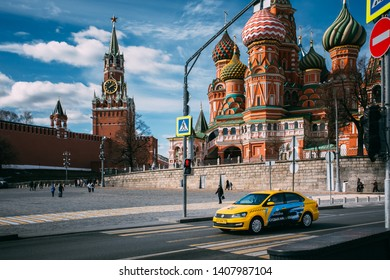 Moscow, Russia - March 28, 2019: Yellow Colour Taxi Car Driving Near Moscow Kremlin And Saint Basil's Cathedral On Red Square. Trip To Famous And Popular Moscow Landmarks. UNESCO World Heritage Sites.
