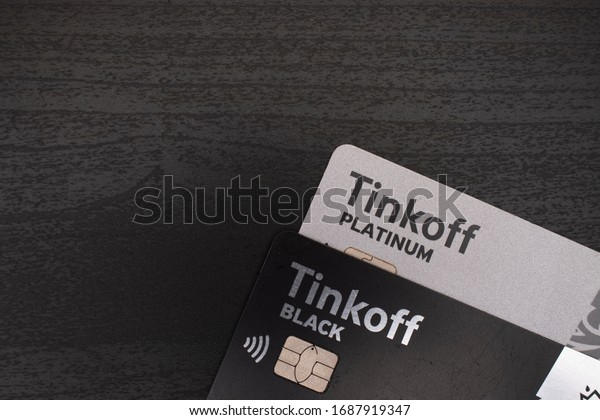 Moscow / Russia - March 30 2020:   Bank cards, Tinkoff black and Tinkoff platinum on a wooden background