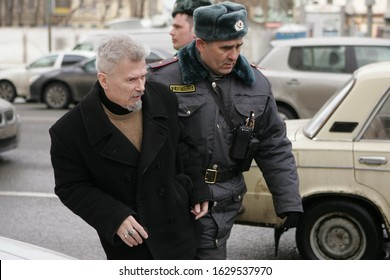 Moscow, Russia - March 31, 2013: Russian writer and political dissident Eduard Limonov is being detained by police officer during an opposition rally