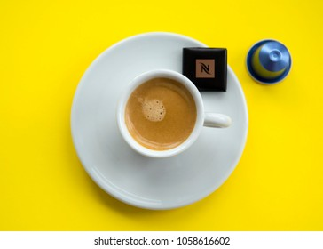 MOSCOW, RUSSIA - MARCH 31, 2018: Cup of Coffee and Nespresso Dark Chocolate Square and Nespresso Coffee Capsule on Yellow Background Top View Natural Light Selective Focus