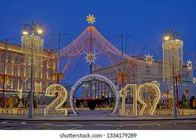 MOSCOW, RUSSIA - Maslenitsa decorations and New Year sign 2019 under the huge illuminated tent topped with sun, symbol of the ancient Russian holiday, framed with the festive street lights in twilight