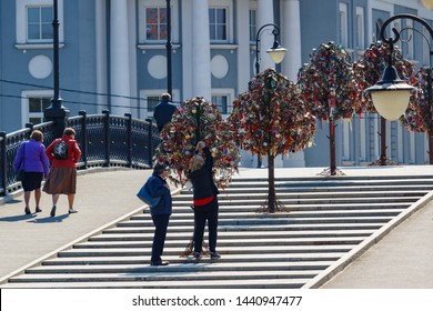 Moscow, Russia - May 01, 2019: Man and woman hang a padlock on a Tree of love on the Tretyakovskiy Bridge (Luzhkov Bridge) in Moscow at sunny morning