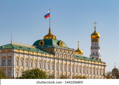 Moscow, Russia - May 01, 2019: View of Grand Kremlin Palace with waving flag of Russian Federation and Ivan the Great Bell Tower of Moscow Kremlin on a blue sky background