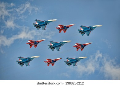 "MOSCOW, RUSSIA – May 04, 2019 Military aerobatics teams of Russian Air Force ""Strizhi"" (Swifts) on 4 red MiG-29 (Fulcrum) and ""Russkiye Vityazi"" (Russian Knights) on 5 blue Su-30SM over Red Square."
