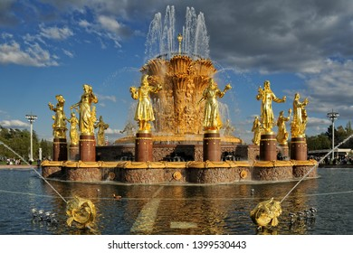 "MOSCOW, RUSSIA - May 04, 2019 Shinning gold fountain ""Friendship of Nations"" with sculptures of women representing republics of USSR after restoration on at VDNKh park under grey clouds at sunset."