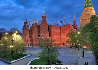 MOSCOW, RUSSIA - May 04, 2019 View from Manezhnaya square on illuminated red brick building of State Historical Museum framed by trees and old-style street lights in morning twilight in spring season.
