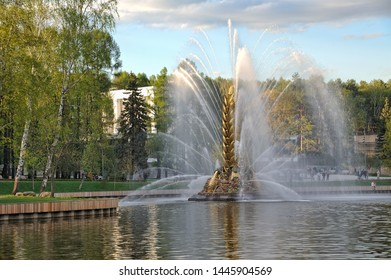 "MOSCOW, RUSSIA - May 04, 2019 Beautiful view on one of the most spectacular fountains at VDNKh ""The Golden Spike"" in the Kamensky Pond framed by trees in spring sunset."