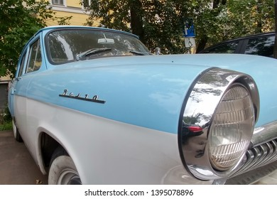 Moscow, Russia - May 05, 2019: The rare, restored Soviet car Gas 21 Volga. A blue and white bi-color oldtimer is parked on the street. Headlights close up