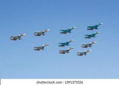 Moscow, Russia - May 07, 2019: Fighters Su-35S and Su-30SM with bombers Su-34 in the blue sky over Red Square in the group Tactical Wing. Aviation part of Victory parade 2019 in Moscow