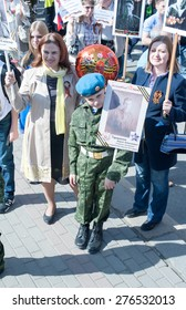 MOSCOW, RUSSIA - MAY 09, 2014: A boy wearing soldier's uniform holds portrait of his grandfather who fought in WWII.  March of 'Immortal Regiment'