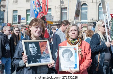 MOSCOW, RUSSIA - MAY 09, 2014: Women with portraits of their relatives during march of 'Immortal Regiment' in Moscow to honor relatives who fought in WWII