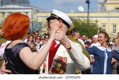 MOSCOW, RUSSIA - MAY 09: War veteran dances on the Theater Square, by the Bolshoi Theater. Victory Day celebration on May 09, 2013 in Moscow.