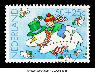 MOSCOW, RUSSIA - MAY 13, 2018: A stamp printed in Netherlands shows Boy on a flying snowman, Children Stamps - Year of the Disabled serie, circa 1983