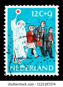 MOSCOW, RUSSIA - MAY 16, 2018: A stamp printed in Netherlands shows Lollipop man guiding children, Children Stamps - Year of the Disabled serie, circa 1959