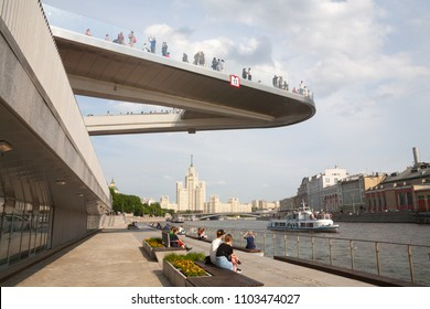 MOSCOW, RUSSIA - MAY 17, 2018: People resting on Moskvoretskaya embankment under Floating bridge. Moskvoretskaya Embankment is major street, located in central Moscow.
