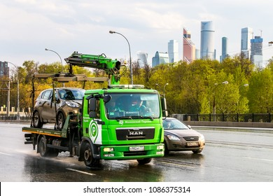 Moscow, Russia - May 2, 2018: Green rescue service truck MAN TGL in the city street at the background of the Moscow International Business Center.