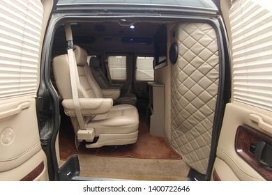 Moscow, Russia - May 2, 2019: GMC Savana/ Chevrolet Express tuning interior. Custom tuned interior with telephone, sound system and tv. White leather inside of car, Chairs with massage