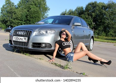 Moscow. Russia - May 20, 2019: Silver Audi A6 S line is parked on outdoor. Near sits the girl is the owner of the car in black t shirt with audi logo