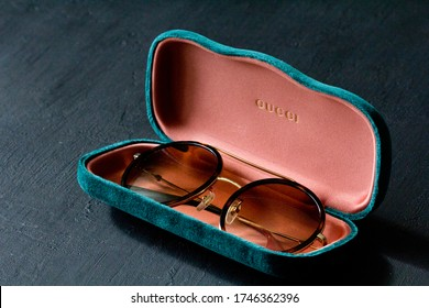 Moscow, Russia, May 20, 2020. Gucci sunglasses are popular high-end brand, created for men, women, with round dark lenses lie on background of green case, on black background. Image shows Gucci logo.
