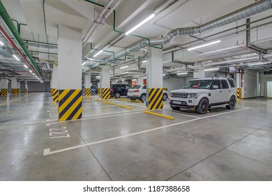 Moscow, Russia - May 2018: Modern underground parking with cars. Signs and boards indicating directions and name of street (Lazorevyy Proyezd).