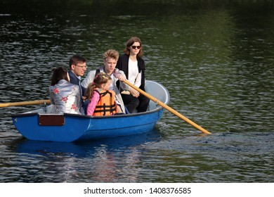 Moscow, Russia - May 2019: Family rides on rowing boat on a lake in Izmailovo park. Parents with children having fun, leisure on a water