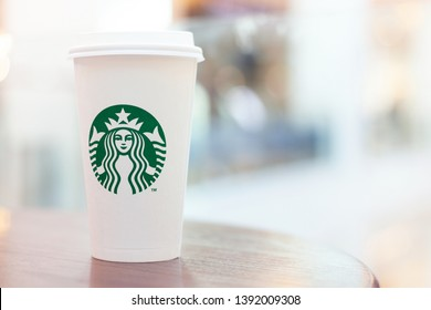 Moscow, Russia - May 2019: Starbucks Coffee Paper Cup With Starbucks Logo Closeup Against Blurred Interior Of Starbucks Coffee Shop.