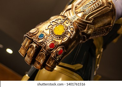 Moscow, Russia - May 2019: Сlose-Up Of Thanos's Infinity Gauntlet. Huge Gold Glove With Infinity Gems. Thanos - Character Of Fortnight Game, Comic And Marvel Movie, Production By Marvel Studio.