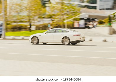 Moscow, Russia - May, 2021: side view of white Mercedes AMG GT 4-Door Coupe. Fast moving car on the street. Vehicle driving along the street in city with blurred background.