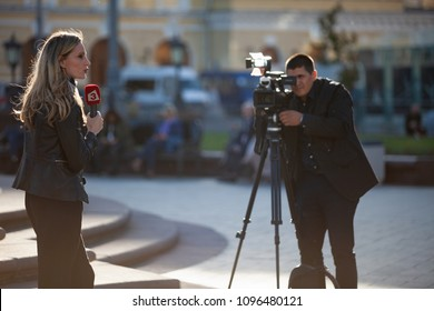 """MOSCOW, RUSSIA - May 21, 2018: The film crew of the Bulgarian TV channel Kanal 3 shoots a report near the Bolshoi Theater. A woman is a journalist with a microphone which has a red logo a white """"3""""."""