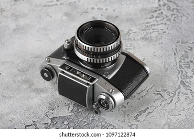 MOSCOW, RUSSIA, MAY 23, 2018. The old German 35 mm SLR camera Exa-1a with Carl Zeiss lens Tessar 2,8/50, released 1974 in East Germany on a grey cement background.