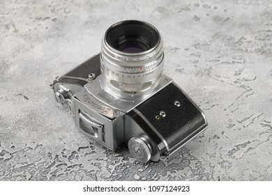 MOSCOW, RUSSIA, MAY 23, 2018. The old German 35 mm SLR camera Exakta (Exacta) with Soviet lens Helios-44, released1947 in Soviet occupied Germany on a grey cement background.