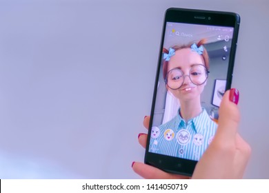 MOSCOW, RUSSIA - MAY 24, 2019: Woman using Snapchat multimedia messaging app with 3d face mask filter on smartphone at home. Face detection technology, AR, social media, selfie, entertainment concept