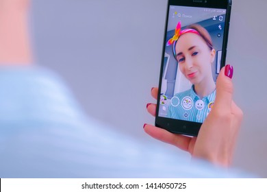 MOSCOW, RUSSIA - MAY 24, 2019: Snapchat multimedia messager with 3d face mask filter on smartphone in woman hands at home. Face detection technology, AR, social media, selfie, entertainment concept