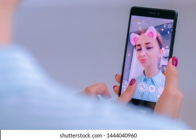 MOSCOW, RUSSIA - MAY 24, 2019: Snapchat multimedia messager with 3d face mask filter on smartphone in woman hands at home. Face detection, AR, beauty, selfie, vogue, fashion, trendy concept