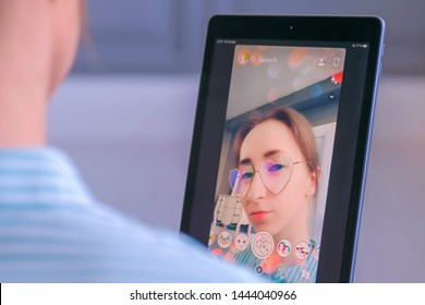 MOSCOW, RUSSIA - MAY 24, 2019: Woman using Snapchat multimedia messaging app with 3d face mask filter on tablet at home. Face detection, AR, beauty, selfie, vogue, fashion, trendy concept