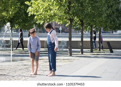 Moscow, RUSSIA - MAY 25, 2018: Boy and girl stand barefoot near fountain