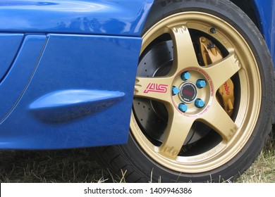 Moscow, Russia - May 25, 2019: Blue subaru WRX STI on the grass, Close up of light alloy wheel in golden color