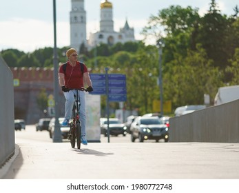 Moscow, Russia- May 25, 2021: People have active sports exercises on  Moscva river embankment in downtown area in hot spring day. Middle aged man cycling. Front view. Healthy lifestyle concept