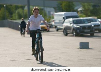 Moscow, Russia - May 25, 2021: People have active sports exercises on the Moscva river embankment in downtown area in hot spring day. Teenager cycling. Front view. Healthy lifestyle concept