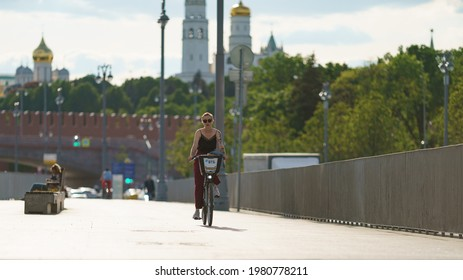 Moscow, Russia- May 25, 2021: People have active sports activity on Moscva river embankment in downtown area in hot spring day. Young woman cycling. Front view. Healthy lifestyle concept