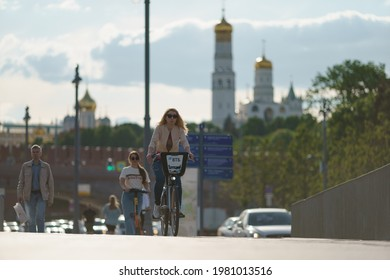 Moscow, Russia- May 25, 2021: People have active sports activity on Moscva river embankment in downtown in hot spring day. Young woman cycling. Other drive motor scooter. Healthy lifestyle concept