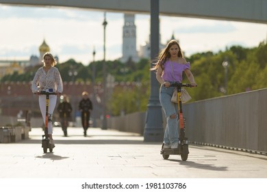 Moscow, Russia- May 25, 2021: People have active sports activity on Moscva river embankment in downtown in hot spring day. Driving of renting motor scooters. Front view. Healthy lifestyle concept