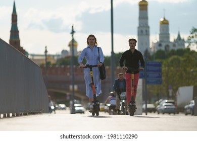 Moscow, Russia- May 25, 2021: People have sports activity on Moscva river embankment in downtown in hot spring day. Driving of renting motor scooters. Front view. Healthy lifestyle concept.