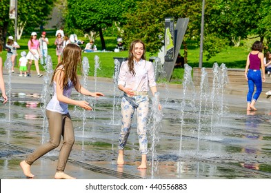 MOSCOW, RUSSIA - May 26, 2016: Two unknown girl bathing in city fountain. Hot summer heat. Girls in wet jeans, skirt and blouse. Wet long hair. Bright emotions on face. Icy freshness, happiness.