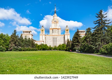 MOSCOW, RUSSIA - MAY 27, 2019: students on green alley with lawn and view of The Main Building of Moscow State University (Lomonosov State University of Moscow) in sunny summer day